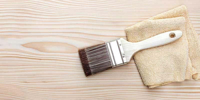 Lyst træ med pensel før træbeskyttelse
